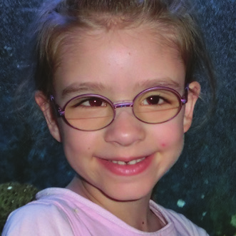 An image of a young girl with aniridia who smiling in front of the camera